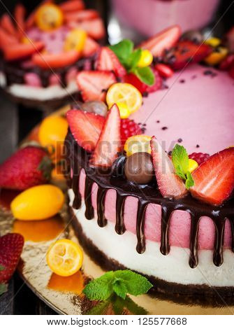 Delicious two-ply strawberry cheesecake (cake) decorated with chocolate and fresh berries