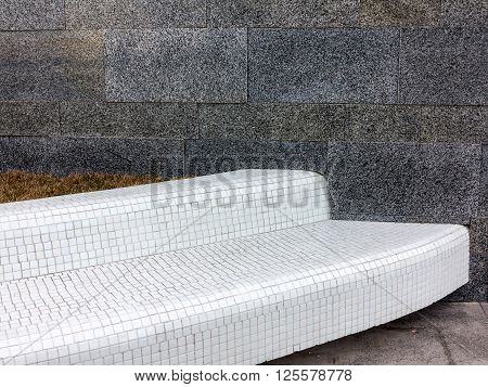 Bench Lined With White Ceramic Tiles On The Background Of A Marble Wall