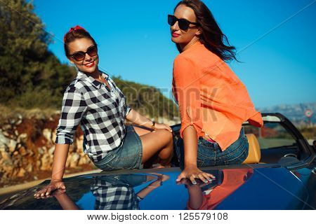 Two young happy girls having fun in the cabriolet outdoors summer vacation concept