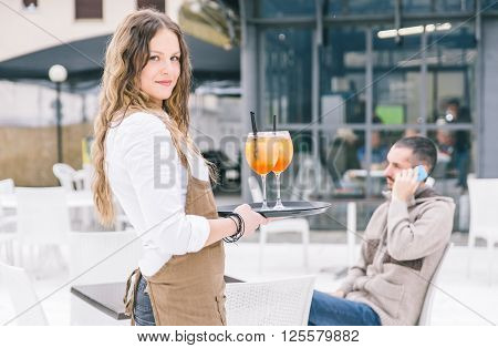 Seductive waitress bring aperitif to the customer.concept about professions and jobs