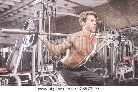 Bodybuilder training hard in the gym. making squat