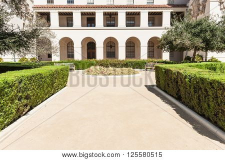 Fromal garden landscape courtyard path lined with manicured hedge leads to round and garden seats in front of two level Spanish style portico