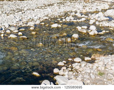 Stones And Mountain River In The Background