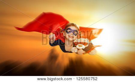 child girl superhero with teddy bear flying through the sky at sunset