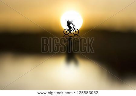 silhouette of cyclist with rucksack on beautiful sunset