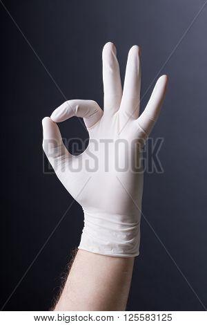 Male hand in latex glove OK sign on dark background