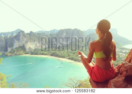 young healthy lifestyle woman practice yoga at seaside rock cliff
