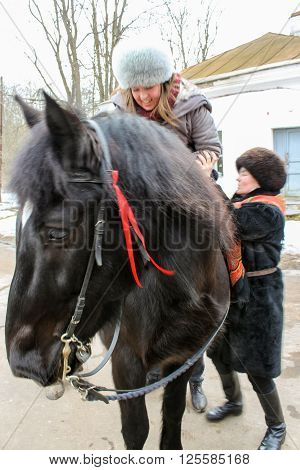 Vitoslavlitsy, Russia - March 12, Woman sitting down on a horse, March 12, 2016. Domestic horses live and work in urban areas.