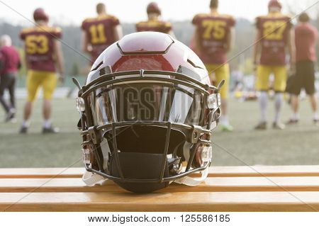 American football helmet on the bench and team in the background