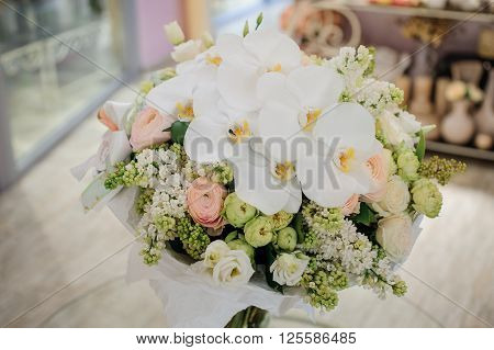 big white bouquet with huge orchids on table