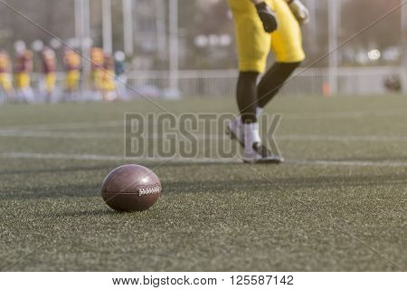 Ball and American football player on the green grass field