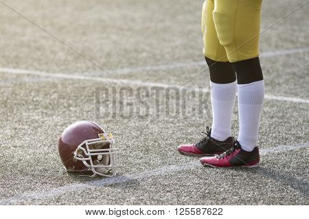 American football player standing on the field next to the sports helmet