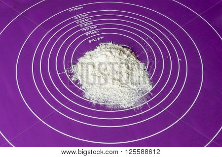 wheat flour as background on a purple silicone mat side view