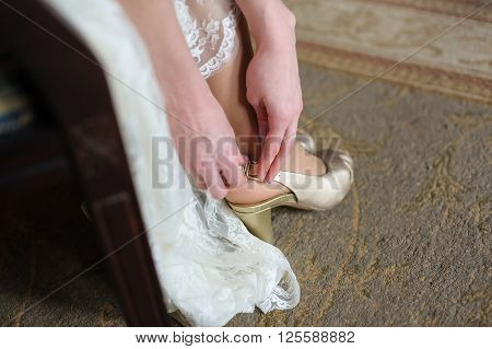 Bride puts on a shoes to a foot  in a room. Woman buttons white shoe.