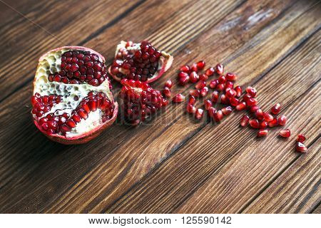 Ripe pomegranate fruit with slices of pomegranate on a wooden table closeup. View from above. Copy space