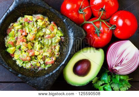 Guacamole - latin american mexican sauce in stone mortar and ingredients on dark background. Top view