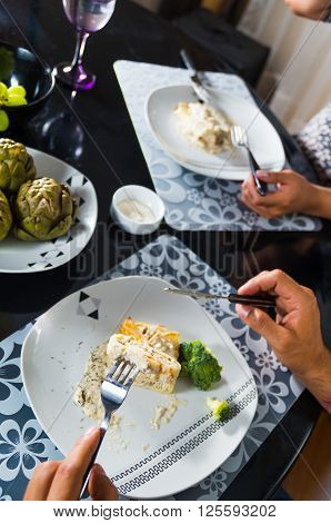 Crepe covered in white sauce lying on plate with broccoli pieces, man eating as seen from above, classy table setting.