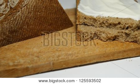 What do You think about bread - and what bread thinks about You? Nugget by nugget. Bread crumb against a background of two slices of bread and a loaf of bread on a chopping Board.
