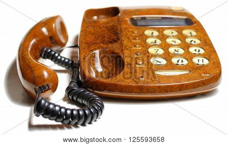 brown phone the handset is near  on a white table