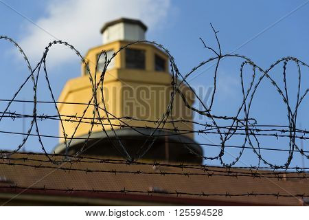 Guarding Tower Behind Barbed Wire Fence Stretched Around Prison Walls