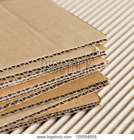 Cardboard pile on corrugated cardboard texture. Industrial background.