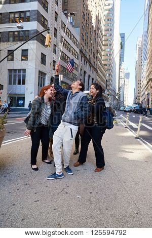 NEW-YORK - CIRCA MARCH 2016: people taking a selfie in New-York. A selfie is a self-portrait photograph, typically taken with acamera phone held in the hand or supported by a selfie stick.
