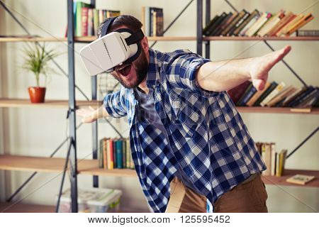 Young Caucasian man flying in virtual reality using modern VR headset glasses