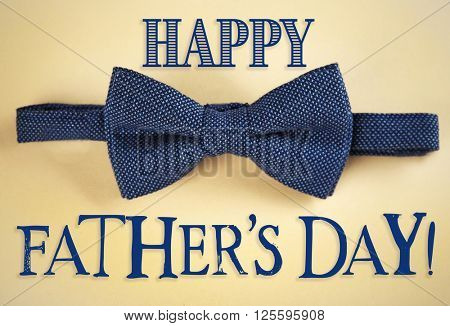 Happy Father's Day. Dark blue bow tie on beige background