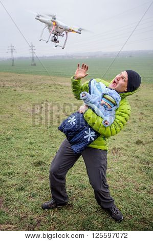 Man protects his baby against an attacking drone. Dangerous drone closeup to frightened parent with infant in arms