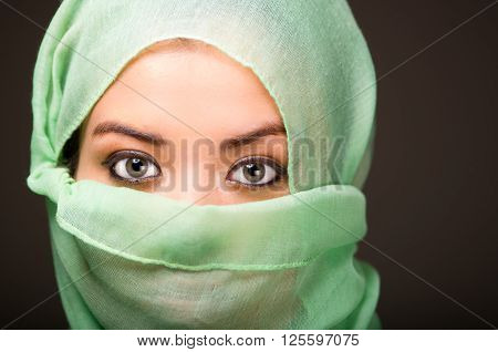 Woman wearing turquoise scarf covering face only revealing beautiful green eyes, grey dark background.