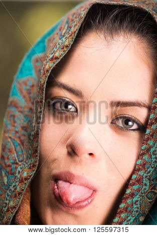Closeup woman wearing blue, grey and brown coloured scarf covering head revealing face, holding tongue out.