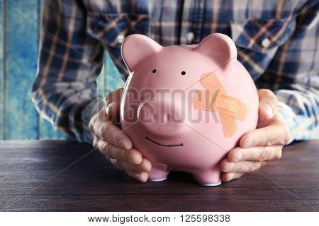 Man holding Piggy Bank with adhesive bandage, on wooden background