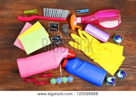 Cleaning set with tools and products on wooden background