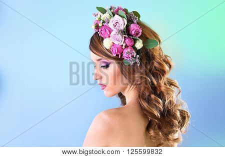 Beautiful young woman wearing floral headband on a blue background