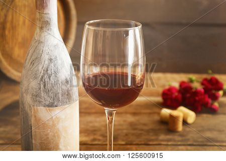 Aged bottle with glass of wine on wooden table