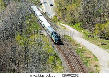 HAMILTON CANADA - MAY 11 2014 - A short VIA Rail passenger train passes through a wooded area. VIA Rail operates Canada's national passenger rail service.