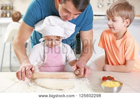 Father's hands helping his son to roll out a dough, close up