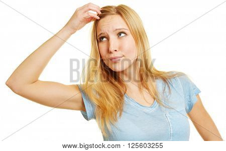 Pensive woman scratching her head while thinking about an idea