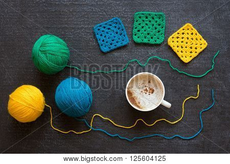 Balls of green, yellow and blue yarn, crocheted motifs and a cup of coffee on grunge black background.