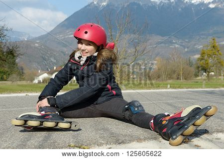 a preteen girl in rollerskate sitting on the road
