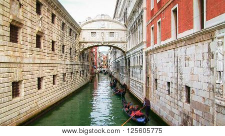 Gondolas on small canal passing towards famous Bridge of Sighs (Ponte dei Sospiri) in Venice Italy.