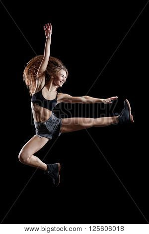 Young beautiful dancer jumping in studio