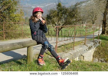 a preteen in roller skate eat an apple on the side of the road