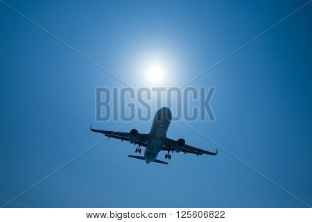 Airplane at take-off with sunrise on blue sky background