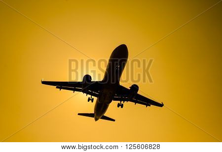 Silhouette airplane at take-off on yellow  background
