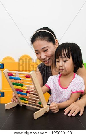Asian Little Chinese Girl And Mother Playing Abacus Together