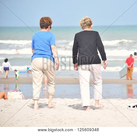 Two Senior Lady Friends Walking through Beach Sand
