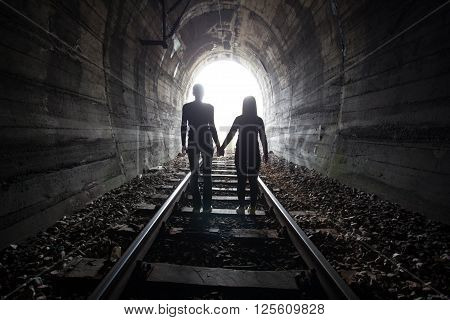 Couple walking hand in hand along the track through a railway tunnel towards the bright light at the other end they appear as silhouettes against the light