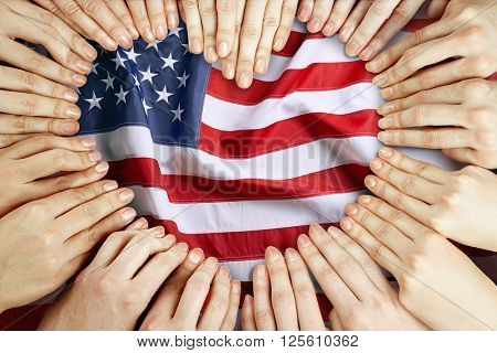 Group of fingers forming heart on USA National Flag background