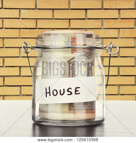 Jar for savings full of banknotes on wall background